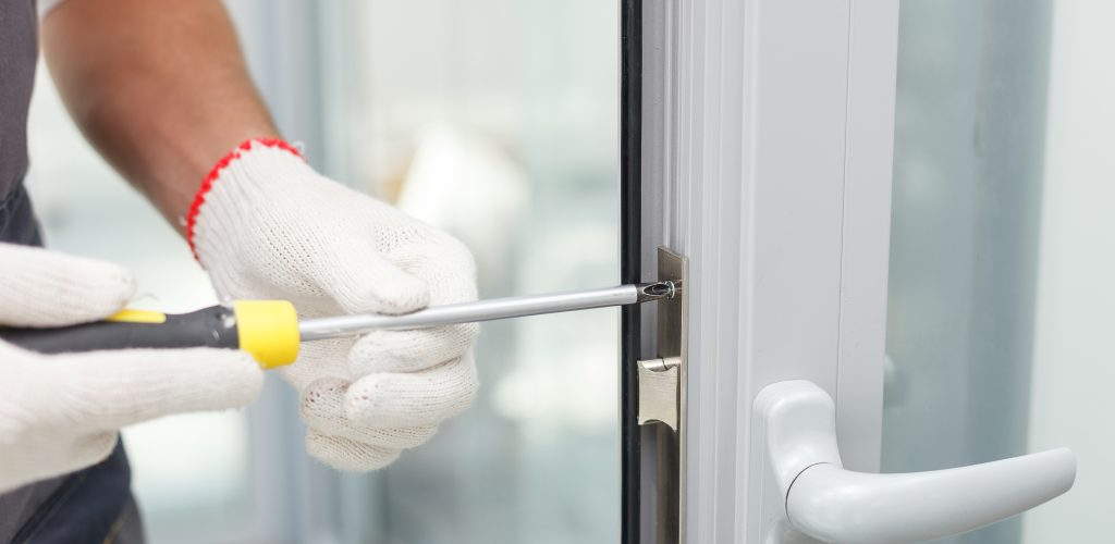 Close up of hands of young carpenter holding a screwdriver and fixing the lock of door. The man is standing in workwear